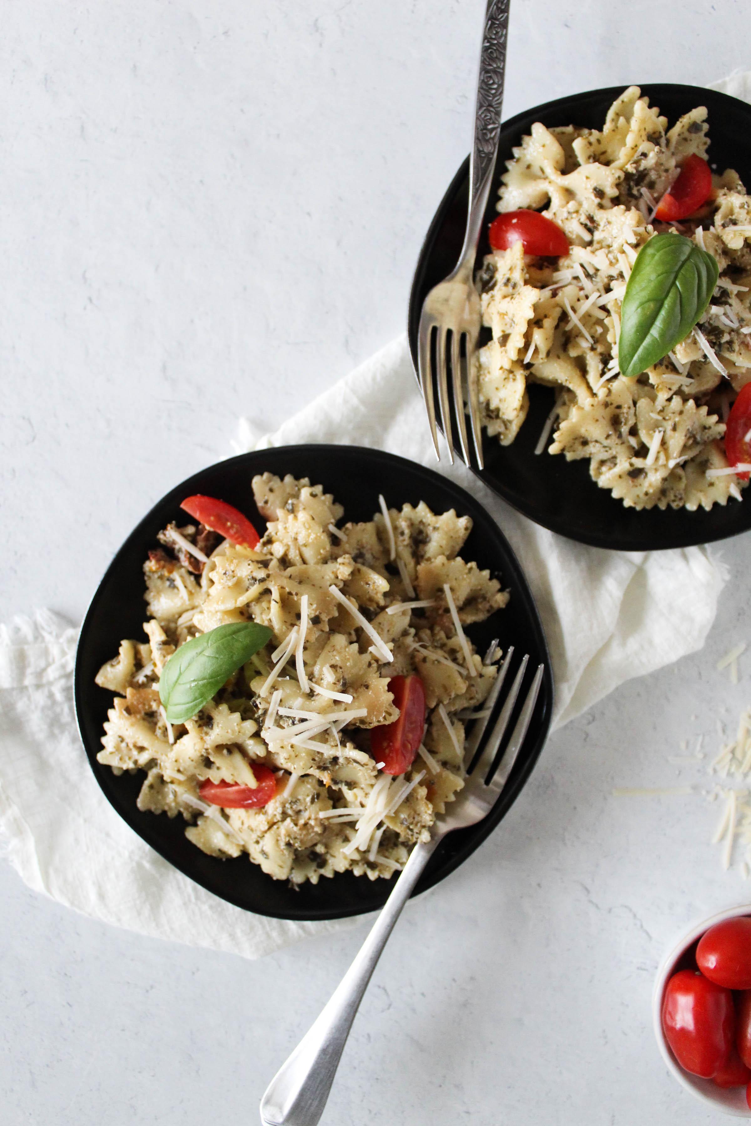 Overhead view of pesto pasta in plates.